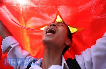 6月12日,在中国驻河内大使馆外,一位身披越南国旗的青年高呼反华口号。法新社